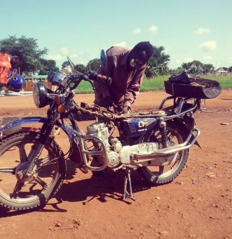 A man examines a broken motorcycle on dark yellow earth against a blue sky