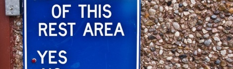 A square blue sign against a gravel wall with white writing: WE APPROVE OF THIS REST AREA. Undeneath, YES or NO, with a button next to each.